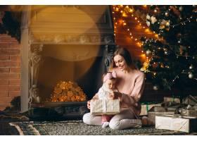 母亲和女儿在圣诞树旁拆开圣诞礼物_3655488