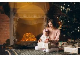 母亲和女儿在圣诞树旁拆开圣诞礼物_3655489