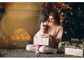 母亲和女儿在圣诞树旁拆开圣诞礼物_3655490