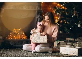母亲和女儿在圣诞树旁拆开圣诞礼物_3655491