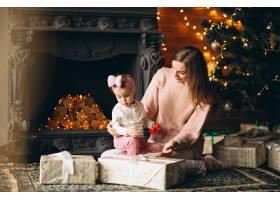 母亲和女儿在圣诞树旁拆开圣诞礼物_3655494