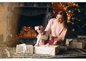 母亲和女儿在圣诞树旁拆开圣诞礼物_3655495