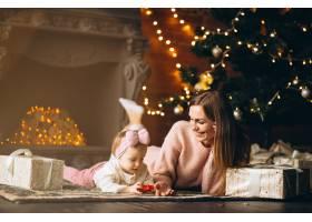 母亲和女儿在圣诞树旁拆开圣诞礼物_3655496