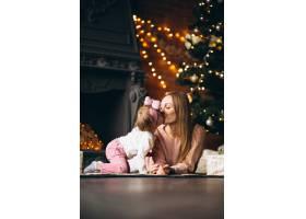 母亲和女儿在圣诞树旁拆开圣诞礼物_3655497