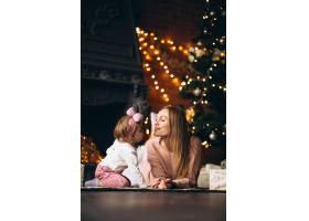 母亲和女儿在圣诞树旁拆开圣诞礼物_3655498