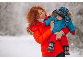 母亲和她的小儿子一起在冬季公园里_3655879