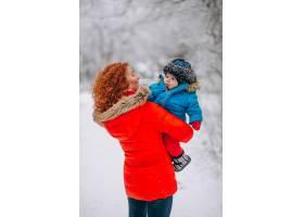 母亲和她的小儿子一起在冬季公园里_3656078