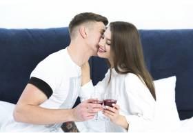 年轻夫妇在床上喝酒_3579924