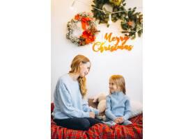 圣诞节前夕母亲带着女儿坐在沙发上_3389596