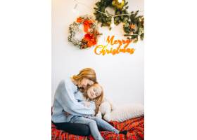 圣诞节前夕母亲带着女儿坐在沙发上_3389601