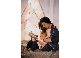 圣诞节母亲带着儿子坐在家里带着灯的舒适_3655267