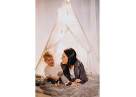 圣诞节母亲带着儿子坐在家里带着灯的舒适_3655268
