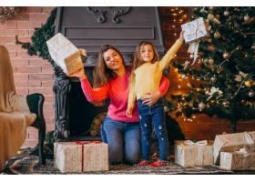 圣诞节母亲带着女儿在壁炉旁打包礼物_3653995