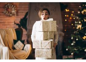 圣诞树前拿着很多礼物的女人_3656005