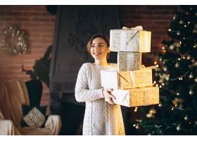 圣诞树前拿着很多礼物的女人_3656007