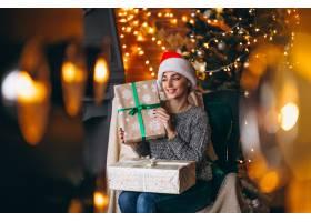 圣诞树旁拿着许多礼物的女人_3655415