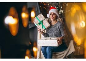 圣诞树旁拿着许多礼物的女人_3655416