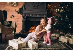 圣诞节母亲带着女儿坐在壁炉旁_3655526