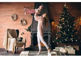 圣诞节母亲带着女儿坐在壁炉旁_3655529