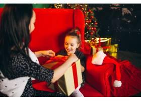 圣诞节母亲带着女儿拿着礼物坐在沙发上_3654145