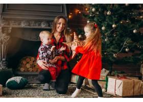 在圣诞树旁带着孩子的母亲_3654263