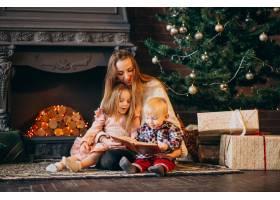 在圣诞树旁带着孩子的母亲_3654288
