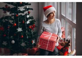 在圣诞树旁拿着圣诞礼物的妇女_3654151