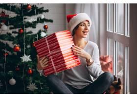 在圣诞树旁拿着圣诞礼物的妇女_3654153