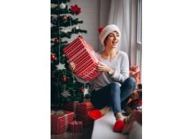 在圣诞树旁拿着圣诞礼物的妇女_3654154