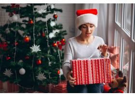 在圣诞树旁拿着圣诞礼物的妇女_3654155