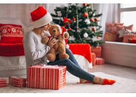 在圣诞树旁拿着圣诞礼物的妇女_3654156