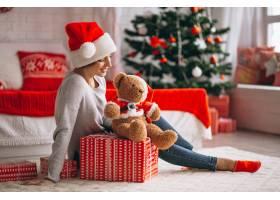 在圣诞树旁拿着圣诞礼物的妇女_3654158