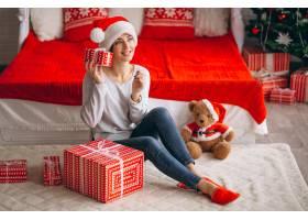 在圣诞树旁拿着圣诞礼物的妇女_3654159