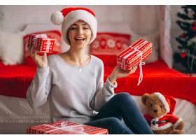 在圣诞树旁拿着圣诞礼物的妇女_3654160