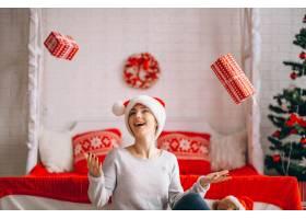 在圣诞树旁拿着圣诞礼物的妇女_3654161