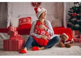 在圣诞树旁拿着圣诞礼物的妇女_3654163