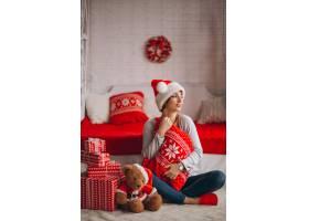 在圣诞树旁拿着圣诞礼物的妇女_3654165