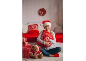 在圣诞树旁拿着圣诞礼物的妇女_3654166