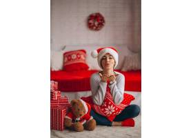 在圣诞树旁拿着圣诞礼物的妇女_3654167