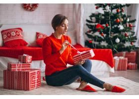 在圣诞树旁拿着圣诞礼物的妇女_3654176