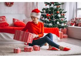 在圣诞树旁拿着圣诞礼物的妇女_3654177