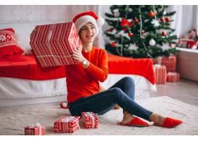 在圣诞树旁拿着圣诞礼物的妇女_3654178