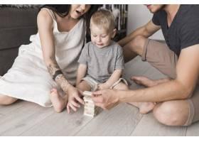 一个小男孩在家里看着父母堆放的木块_3456216