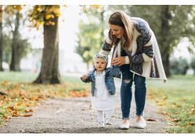 一位年轻的母亲带着她的小女儿在秋天的公园_3202252