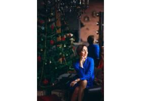 一位穿着漂亮衣服的女子坐在圣诞树旁_3655373