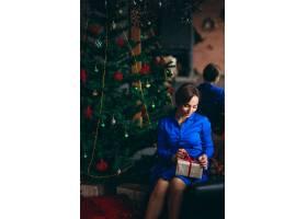 一位穿着漂亮衣服的女子坐在圣诞树旁_3655374