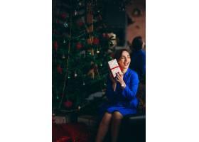 一位穿着漂亮衣服的女子坐在圣诞树旁_3655375