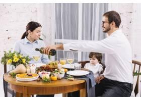 一名男子在与家人共进晚餐时用玻璃杯倒酒_3278982