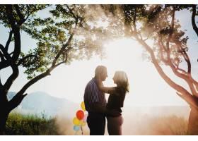 一对可爱的成年夫妇手持五颜六色的气球站在_3711293