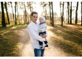 一对年轻夫妇带着一个小男孩走在树林里_3280575